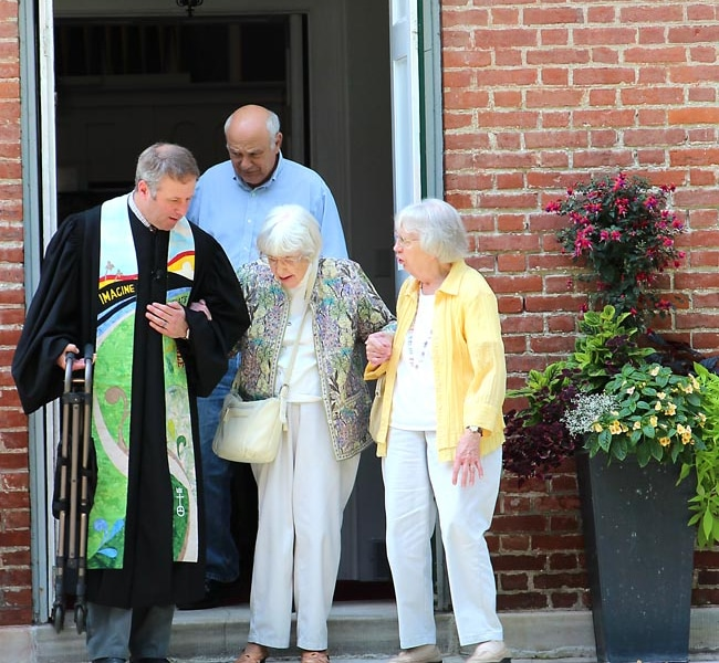 Pastor Brent helps an elderly lady down the stairs of the church