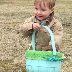 A young boy smiles with delight as he inspects his Easter egg basket