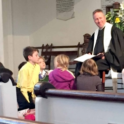 Rev. Brent Damrow smiles at the children surrounding him during his children's message