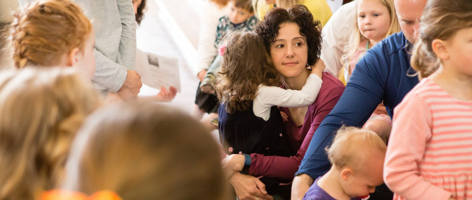 A mother hugs her daughter during the children's sermon. Other parents and children surround them.