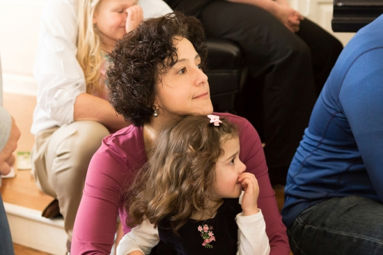 A mother hugs her daughter while they listen to the children's sermon