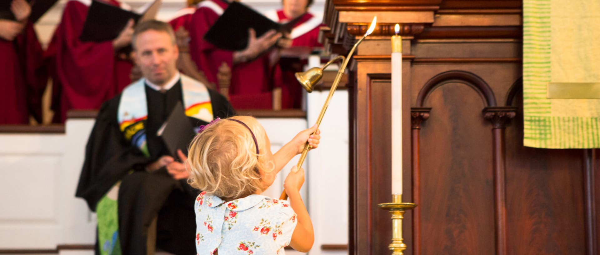 A young girl lights a candle to begin worship