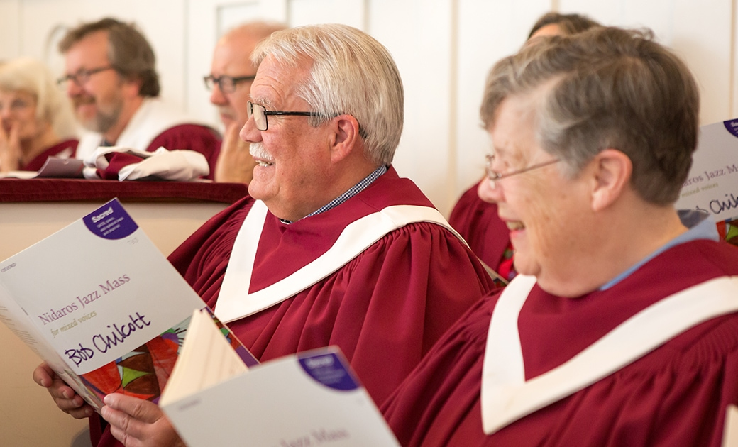 Members of the choir smile while looking at the Minister of Music