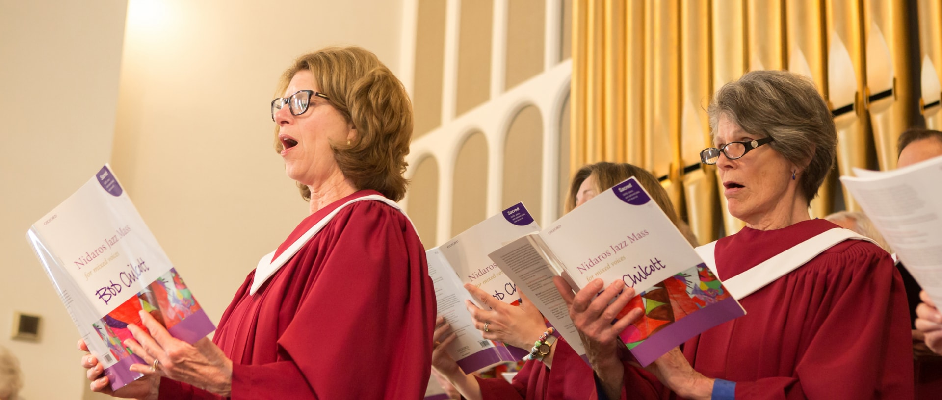 Two women sing the Nidaros Jazz Mass by Bob Chilcott from the organ loft. Organ pipes are visible in the background.
