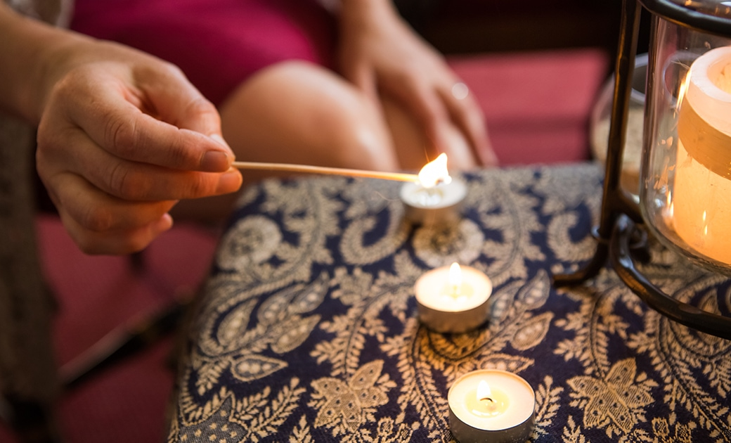 A woman lights a candle in prayer