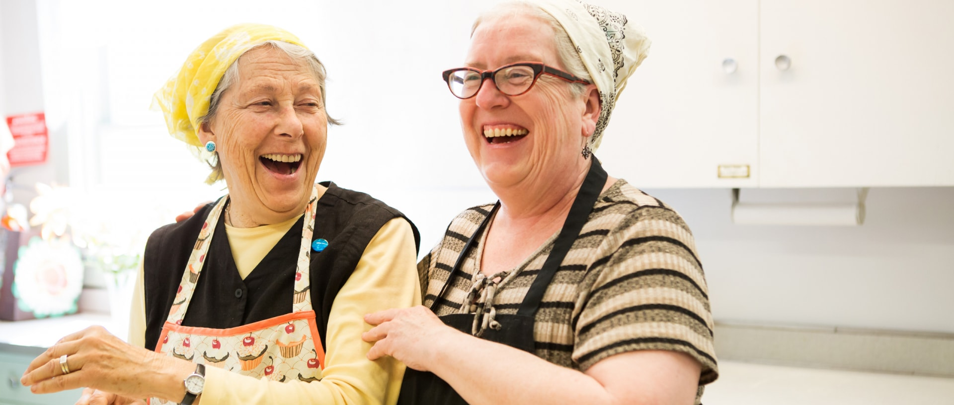 Two women laugh while prepping a meal for Berkshire county's homeless.