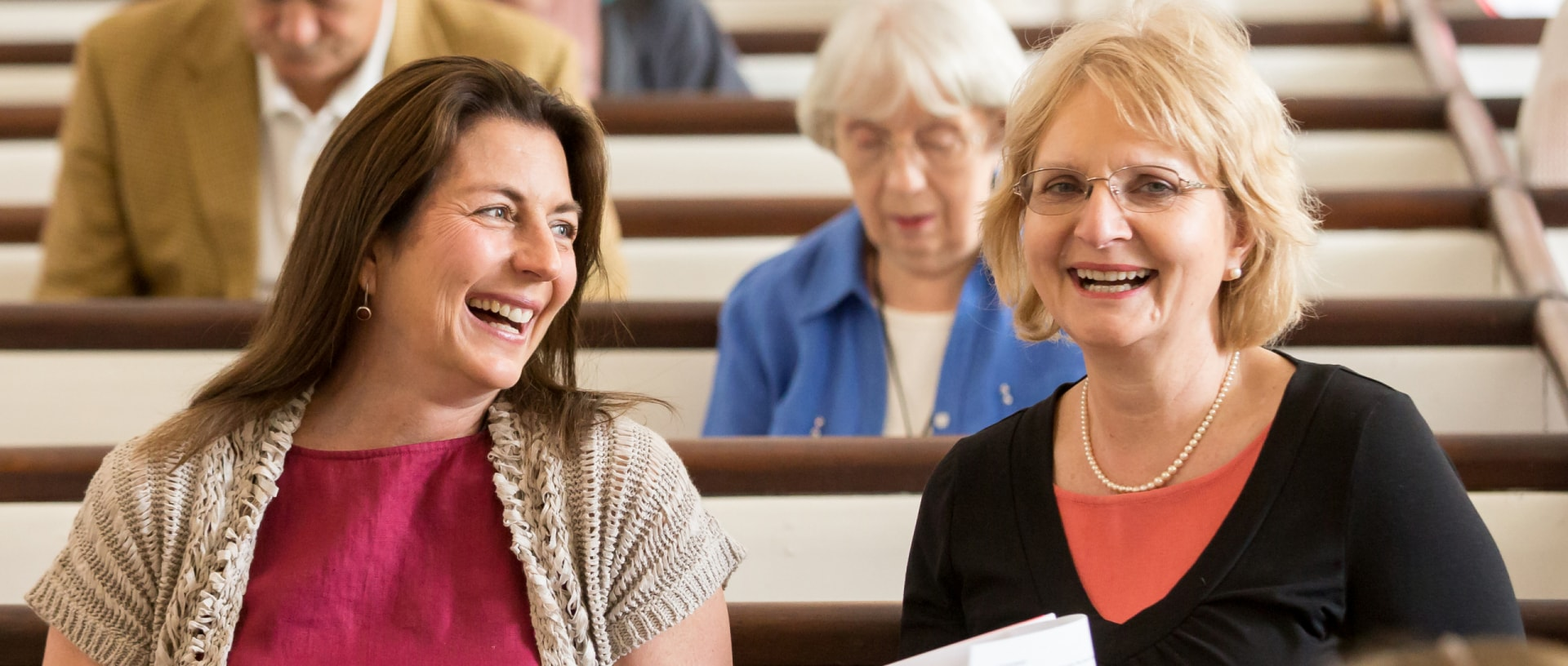 Two women smile in the sanctuary of the Stockbridge Congregational Church