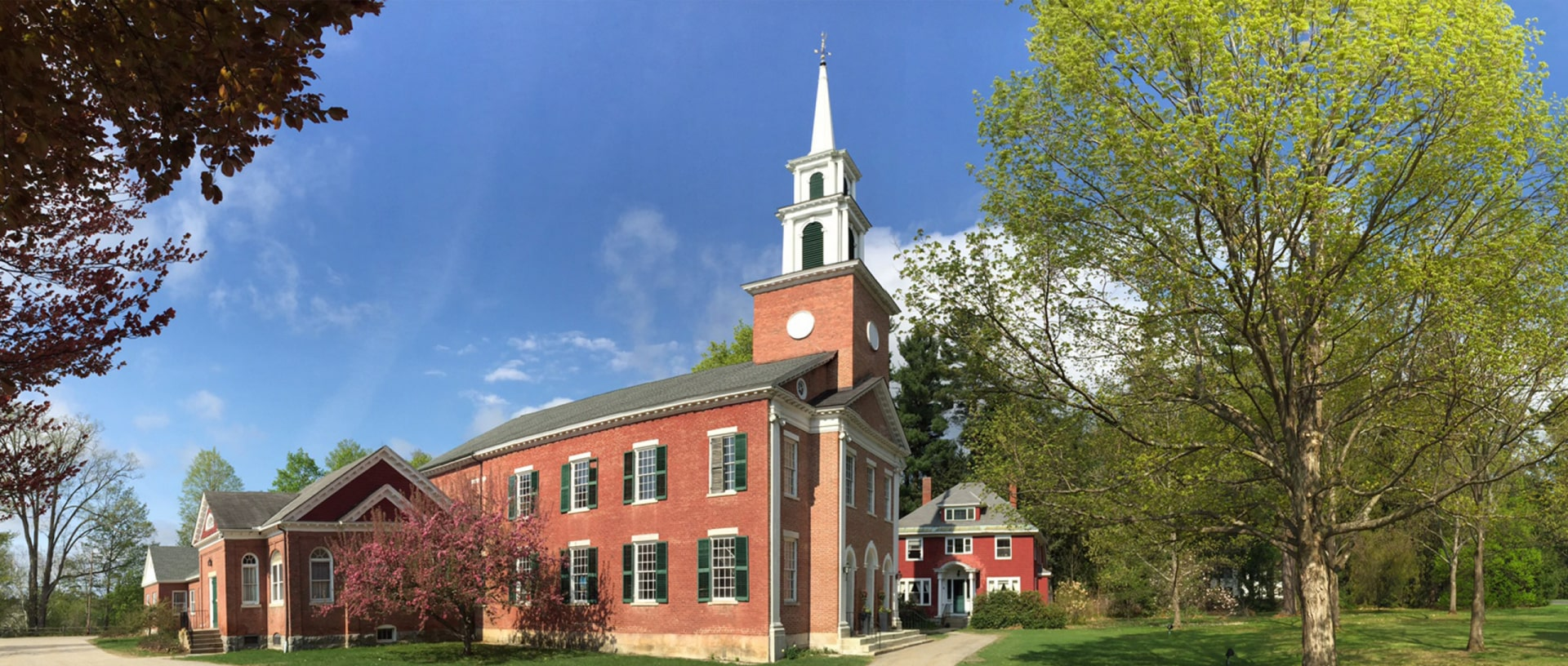 Exterior image of the historic 1824 congregational church in Stockbridge. A brick building with green shutters and a tall white steeple.