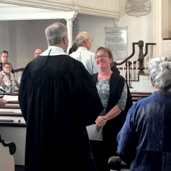 Cathy Schane-Lydon smiles as Pastor Brent Damrow offers a parting blessing