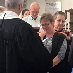 A tearful minister of music receives a blessing from the congregation