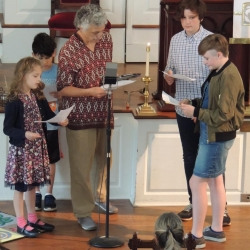 Children and adults perform in a live Sunday School radio play