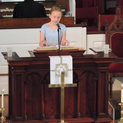 A preteen girl reads from the pulpit