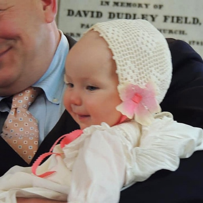 Gwendolyn laughs while her father holds her.