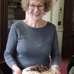 A woman carries a chocolate cake