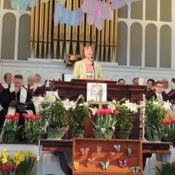 A woman reads from the pulpit