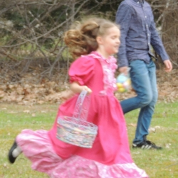 A girl in a pink dress hunts for easter eggs