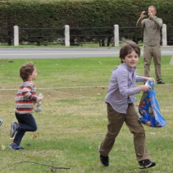 Boys run on the lawn in search of Easter eggs.
