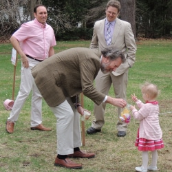 An older man helps a toddler look for Easter eggs