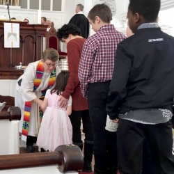 Rev. Patty Fox gives communion to a young girl