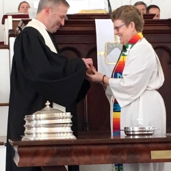 Rev. Brent Damrow and Rev. Patty Fox serve each other communion