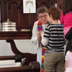 Rev. Patty Fox serves communion to a young boy