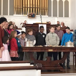 Rev. Patty Fox, children, and their parents gathered around the communion table
