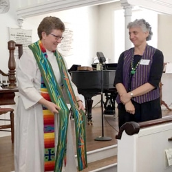 Rev. Patty Fox holds her new clerical stole up before the congregation