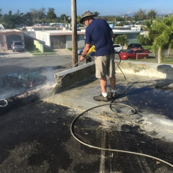 A man power washes a roof