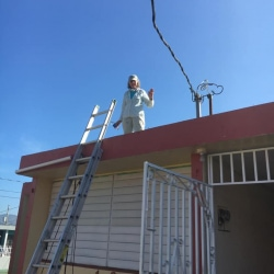 A worker waves from a roof