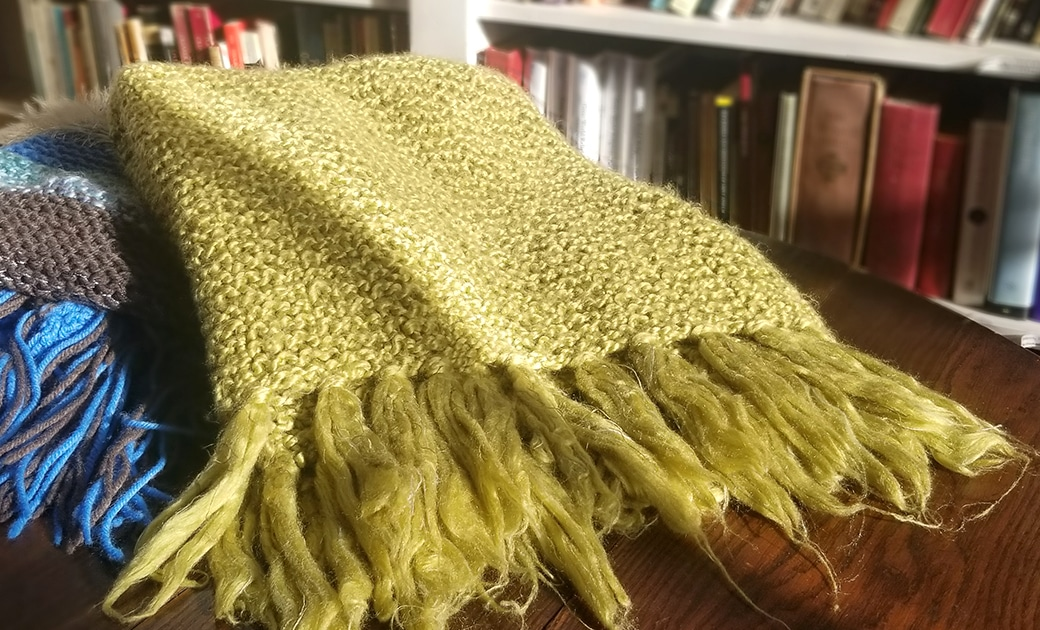 A green prayer shawl and a blue prayer shawl on a wooden table