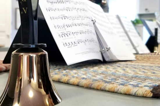 A handbell with sheet music