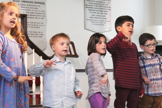 Three boys and two girls sing in church