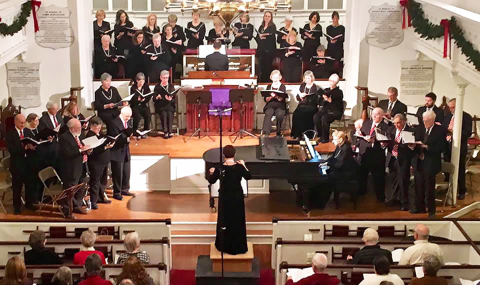 A choral group sings in a church sanctuary