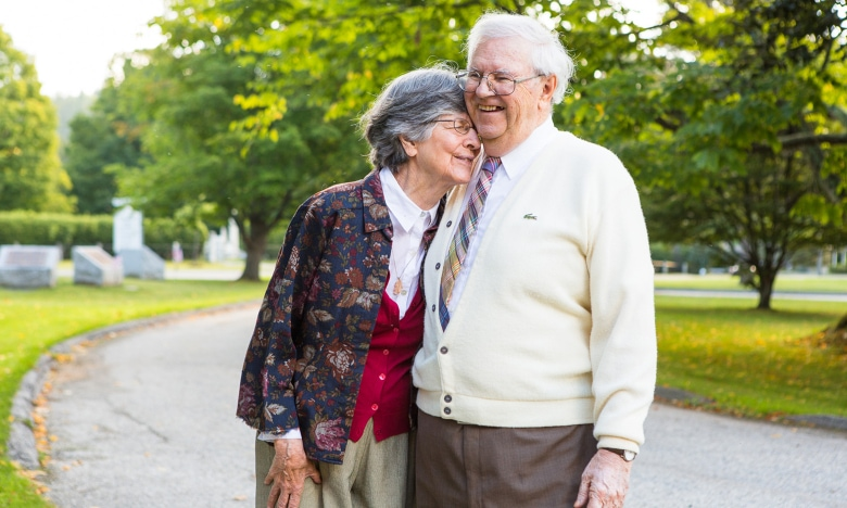 An elderly wife and husband laugh and hug each other
