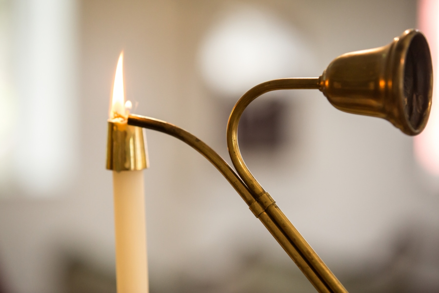 A candle is lit in a church