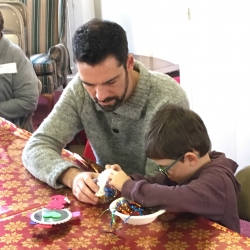 A boy and his father make Christmas ornaments