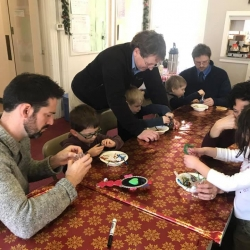 A group of fathers and their children make Christmas ornaments