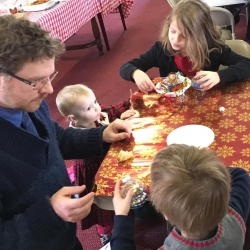 A father and his children make Christmas ornaments
