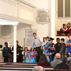 A group of children wearing Halloween costumes in the church sanctuary
