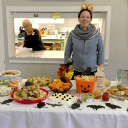 A woman in a costume behind a buffet of Halloween snacks