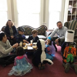 Parents and their children around a table eating snacks