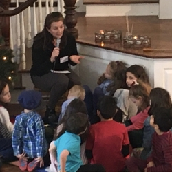 A woman offers the Children's Sermon on refugees to a group of children.