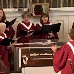 A man leads the church choir in an anthem