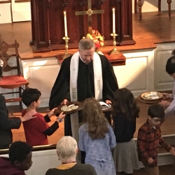 The pastor receives the offering from a group of children