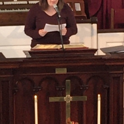 A woman reads the call to worship from the pulpit