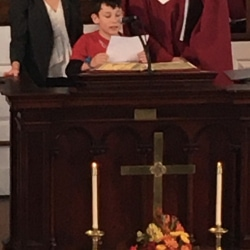 A boy reads scripture from the pulpit while his parents look on