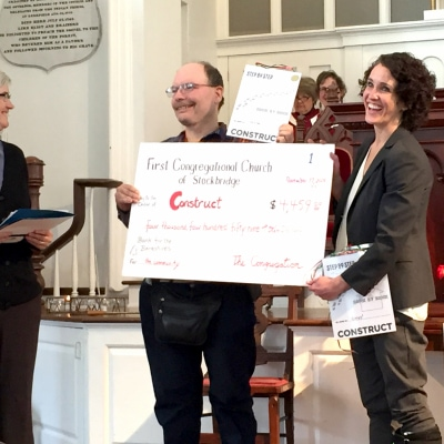 Church members present the Executive Director of Construct with an oversized check to represent a $4,459 donation to Construct from the church