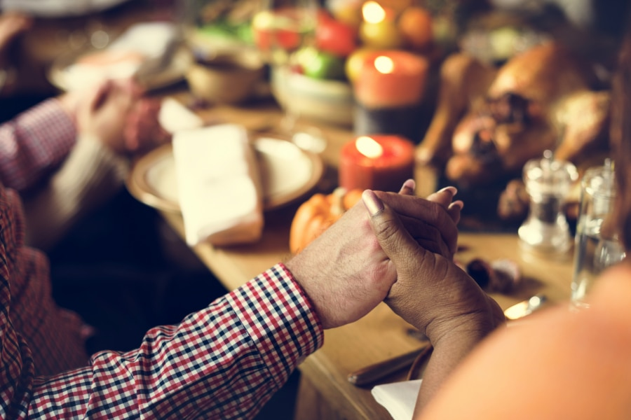People hold hands and pray at the Thanksgiving Dinner Table