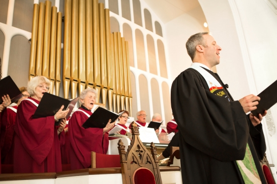 The pastor and members of the church choir sing a hymn