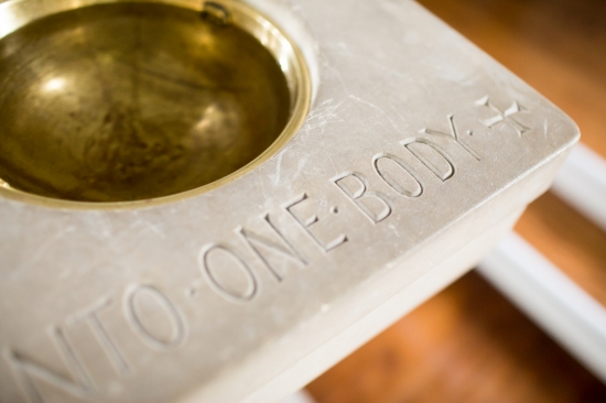"Baptismal font inscribed with the words ""One Body"""